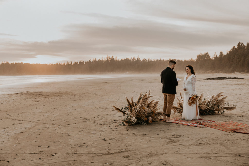 Eloping in Tofino.  Couple on beach with golden sunset behind them.