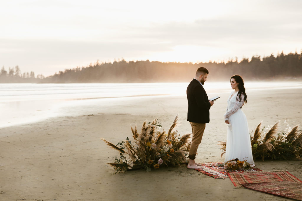 Tofino elopement.  Groom reading his partner wedding vows on beach.