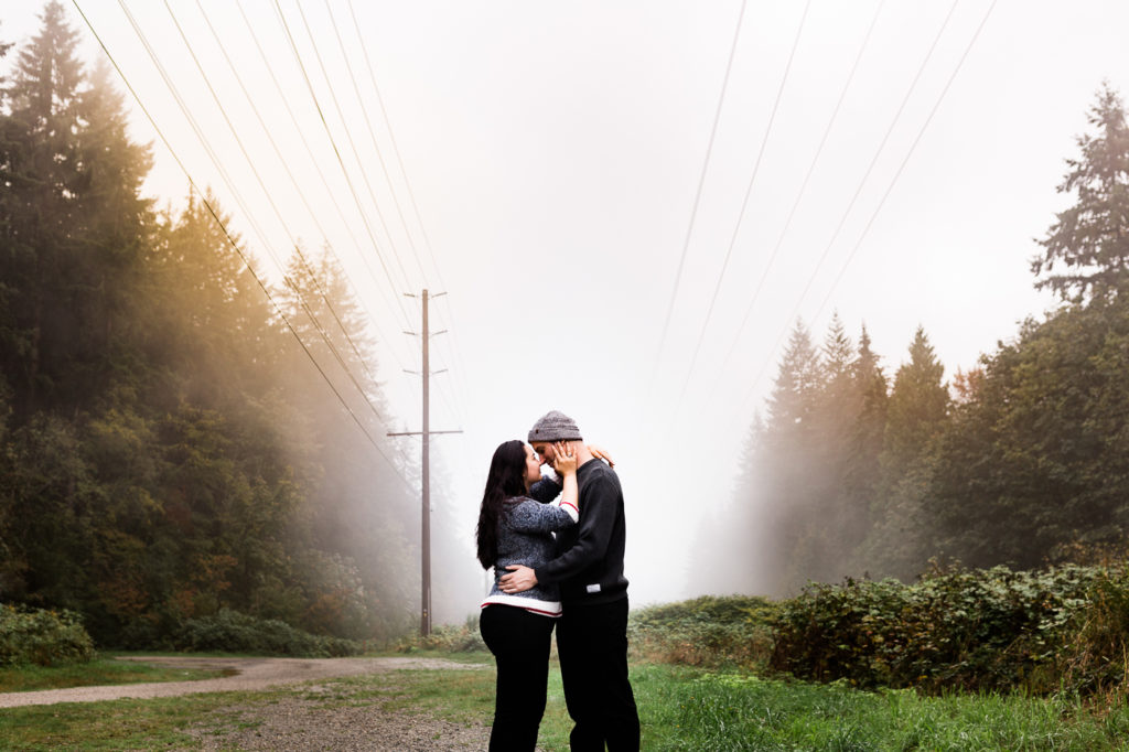 Engagement photography, standing in a misty rainforest, holding each other.