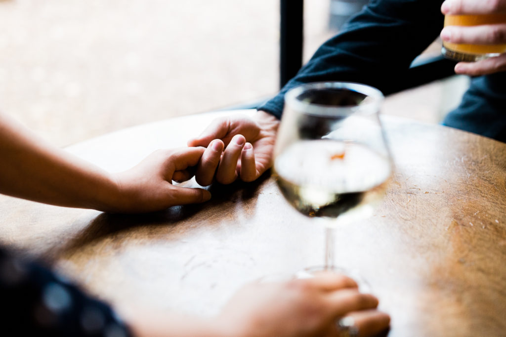 Engagement photography, holding hands while having some drinks.