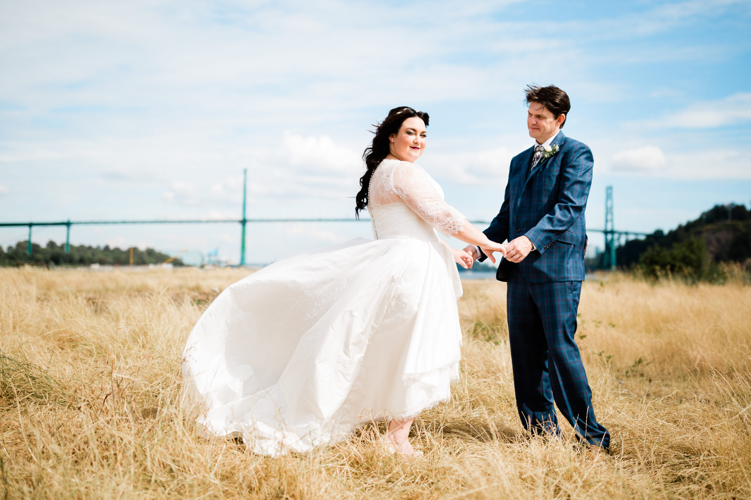 Bride and groom standing in field with Lions Gate bridge behind them.