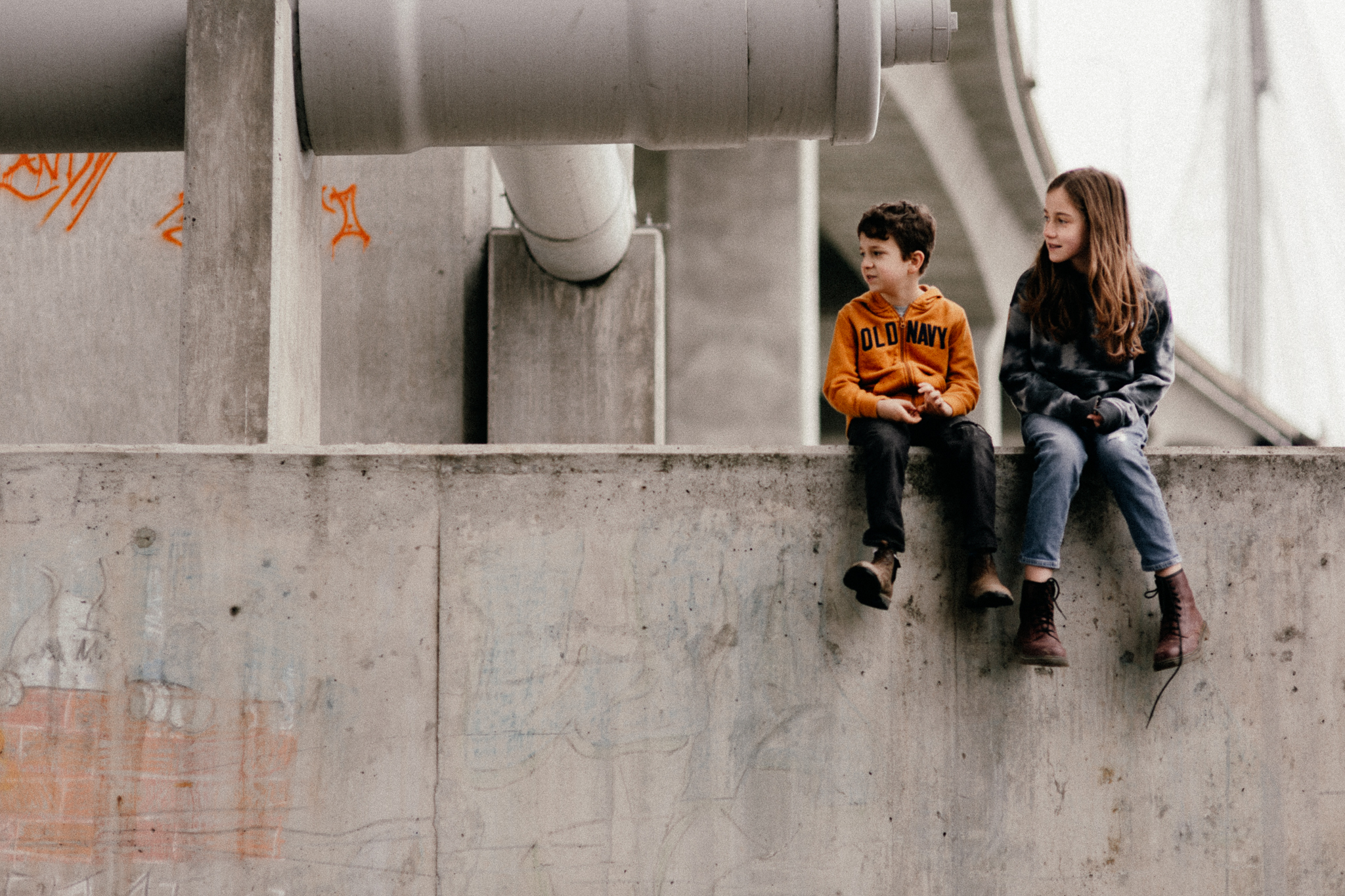 Two kids sitting under a bridge, staring off in the distance.