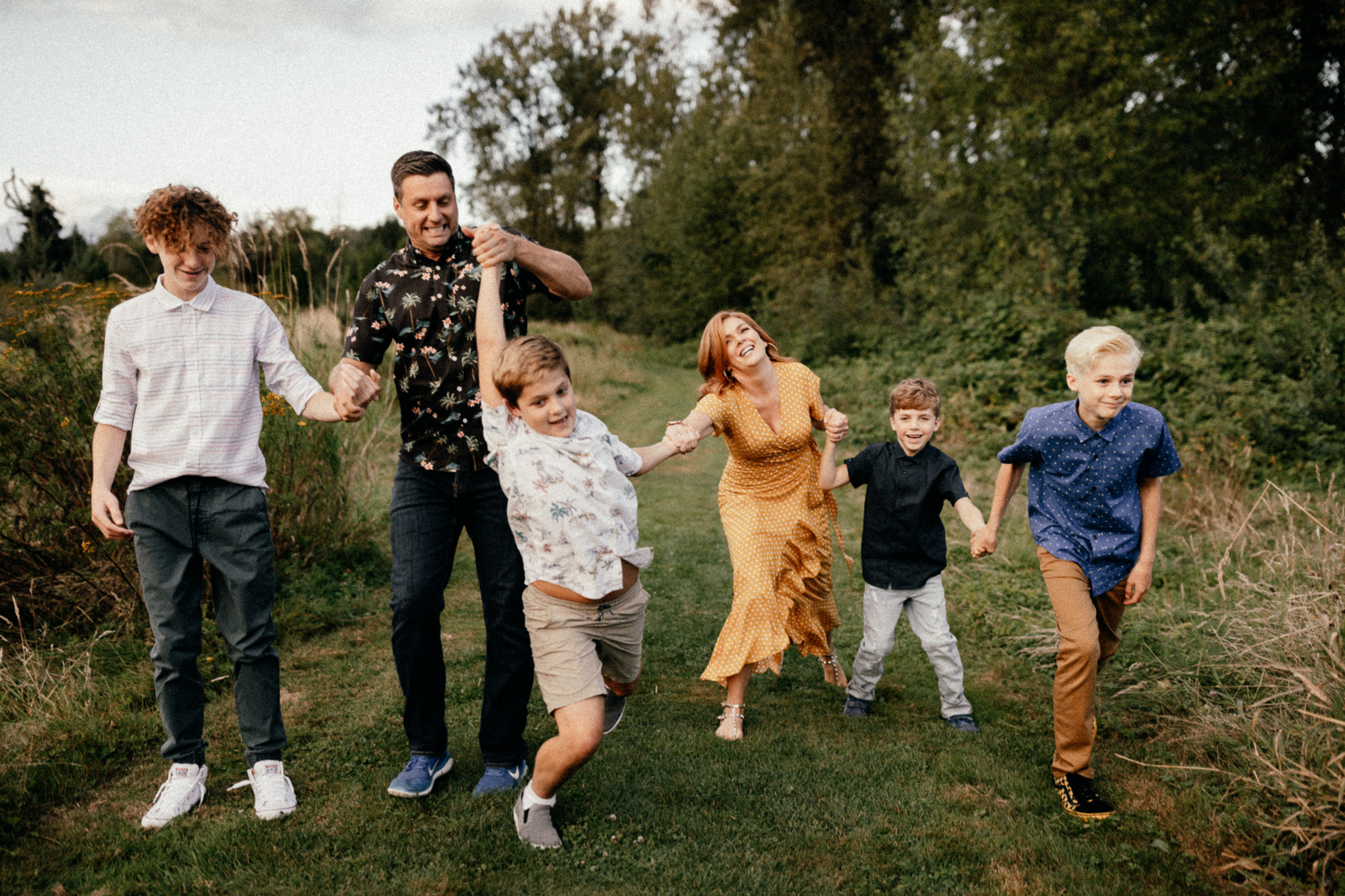 Mom, dad, and four sons walking through the grass and being silly together.
